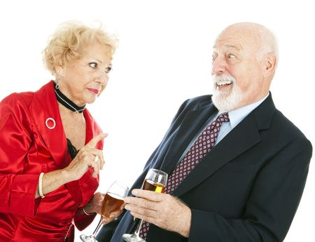 embarassment: Senior couple at a party.  The husband is drunk and the wife is angry at him.  Isolated on white. Stock Photo