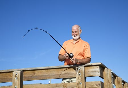 Senior man fishing off a pier.  Horizontal view with room for text.