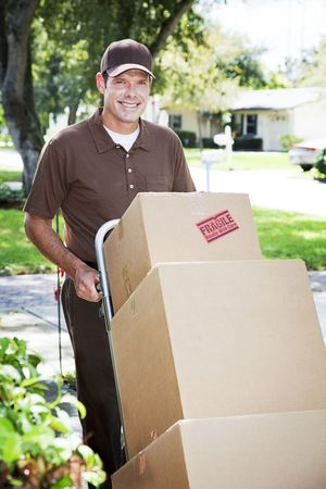 Handsome delivery man or mover pushing a stack of boxes on a dolly, outdoors.   photo