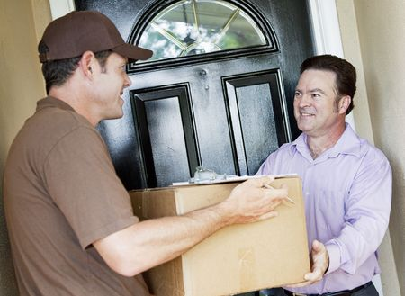 delivery package: Man receiving a package delivery from a courier at his home.