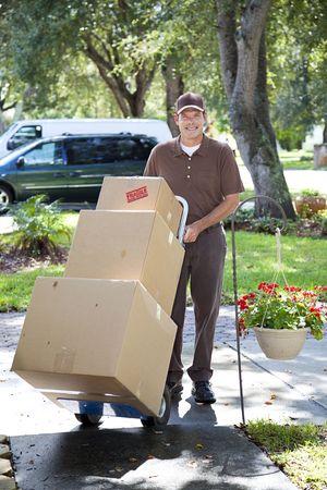 Delivery man or mover bringing boxes up your front walk.   Reklamní fotografie