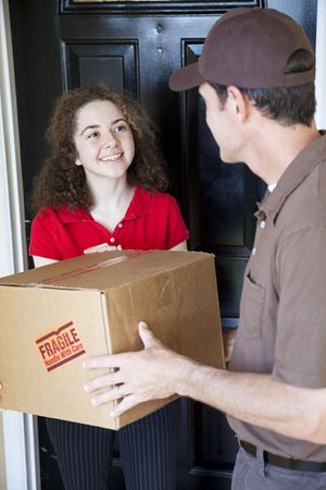 Young woman receives a home delivery from a courrier.   photo