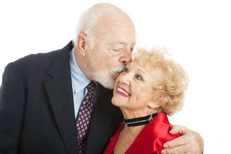dentadura postiza: Adorable mujer senior, recibiendo un beso de vacaciones rom�nticas de su marido.  Aislados en blanco.