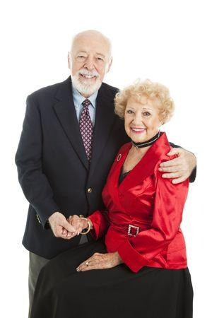 Elegant senior couple posing for a holiday portrait.  Isolated on white. photo