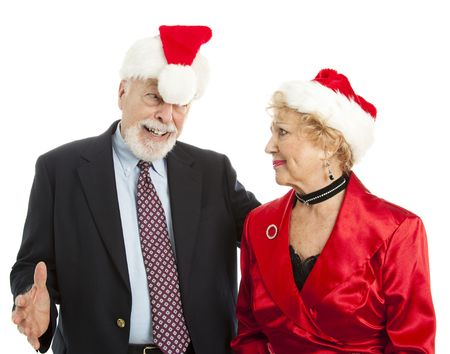 embarassment: Tipsy senior man embarasses his wife at a Christmas party.  Isolated.