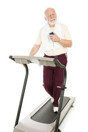 ecoute active: Senior man enjoys music on his mp3 player while he exercises.  Isolated.