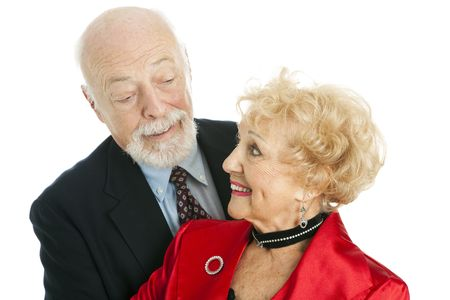 Well dressed senior couple flirting with each other.  Isolated on white. photo