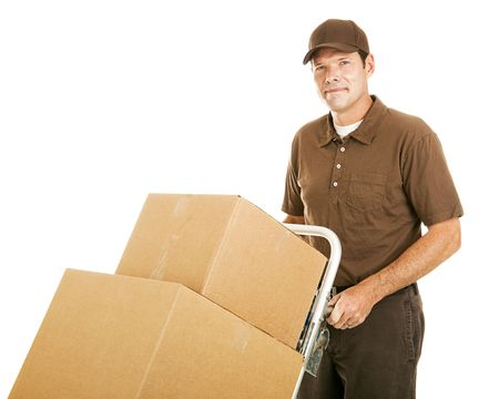 Handsome moving man moves a stack of boxes on his dolly.  Isolated on white. photo