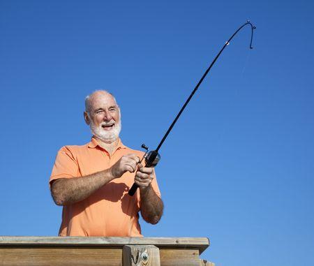 Senior man having a great time reeling in a big fish.