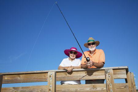Happy senior couple has fun fishing on their Florida vacation.