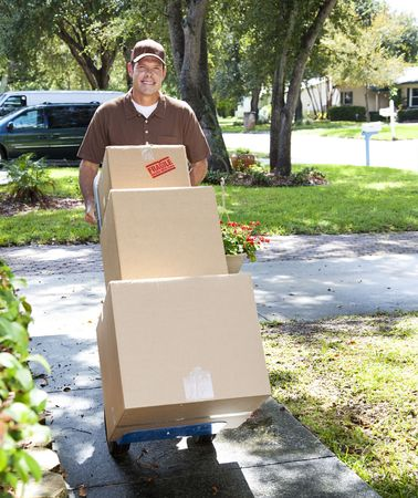 hand truck: Delivery man or mover pushing a dolly loaded with boxes up the front walk.   Stock Photo