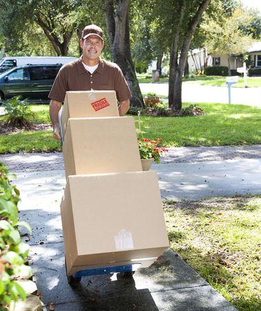 dolly: Uomo di consegna o motore che spinge un carrello caricato con caselle fino a piedi anteriori.   Archivio Fotografico