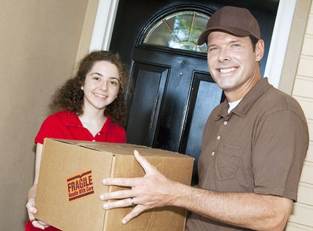 Friendly delivery man handing a package to a customer.  Focus on the man.   Banco de Imagens