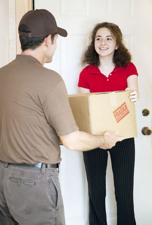 Young woman at home receives a package from a delivery man.