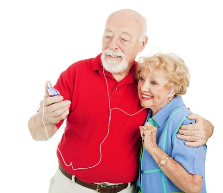savvy: Tech savvy senior couple listens to mp3s on their media player.  Isolated on white. Stock Photo