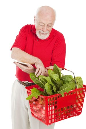 grocery basket: Senior man checking his grocery basket against his shopping list.  Isolated on white.