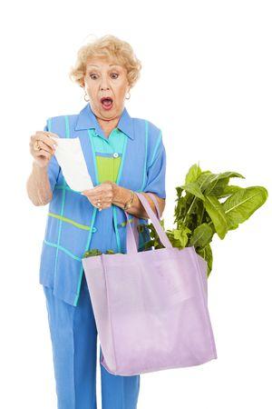 Senior vrouw geschokt door de prijs van groceries.  Geïsoleerd op wit.