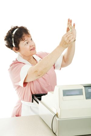 Cashier in a restaurant checks a bill to see if it is counterfeit.  Isolated on white.
