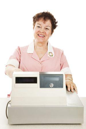 Friendly smiling cashier behind her cash register.  White background.