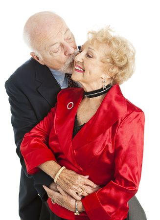 Senior couple dressed for the holidays.  Hes giving her a kiss on the cheek.  Isolated. photo