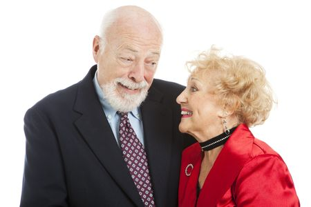 knowing: Beautiful senior couple dressed for the holidays, giving each other a knowing look of romance.  Isolated.