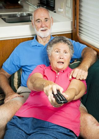 Senior couple watching television in their motor home, shocked by what they are seeing. photo