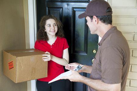 brings: L'uomo di consegna porta a porta di un pacchetto di un cliente e aspetta per una firma. Archivio Fotografico