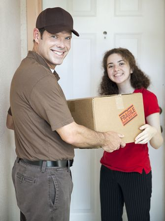 courier: Handsome delivery man smiles as he delivers a package to a customer. Stock Photo
