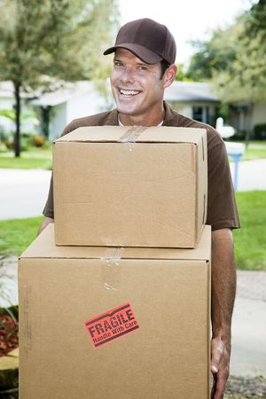 Handsome smiling delivery man carrying packages.   photo