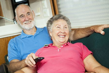 Happy senior couple laughing as they watch TV together in their motor home.   photo