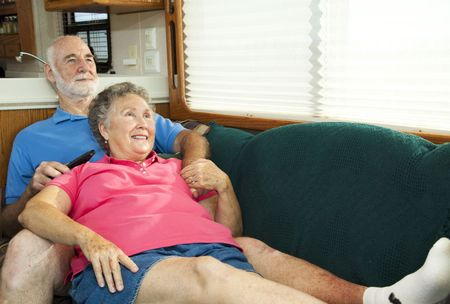 Senior couple relaxes and watches TV on the couch in their motor home. Stock Photo - 6230873