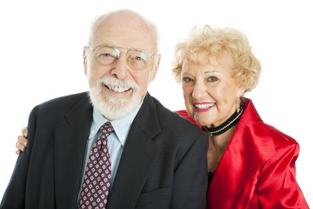 Well-dressed, successful senior couple smiling.  Isolated on white. photo
