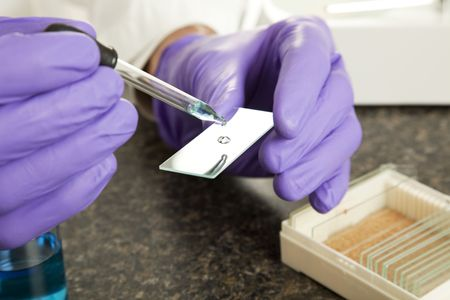 Closeup of a scientist's hands as he drops a sample onto a slide for analysis.