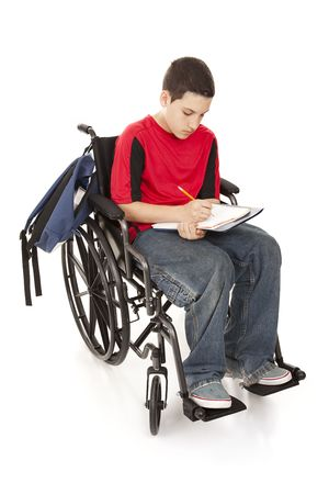 Disabled teenage boy doing homework in his wheelchair.  Full body isolated.