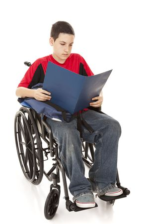 Disabled teen school boy reading in his wheelchair.  Full body isolated. photo