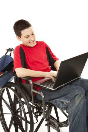 Disabled teen boy using a laptop in his wheelchair.  Isolated on white.