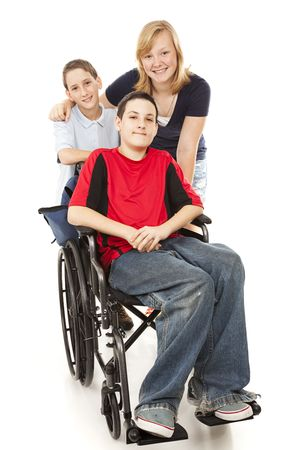 Group of kids with one adolescent boy in a wheelchair.  Full body isolated. photo