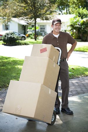 Mover or delivery man arrives with a stack of boxes for you. Stock Photo - 6446790