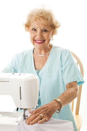Beautiful senior woman enjoys sewing.  Isolated on white.   photo