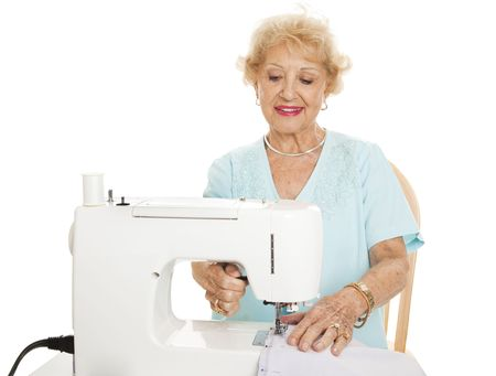 Pretty senior woman using her sewing machine.  Isolated on white. photo