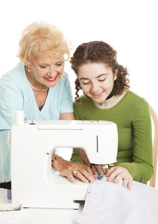 Grandmother teaches her teen granddaughter to use the sewing machine.  White background. photo