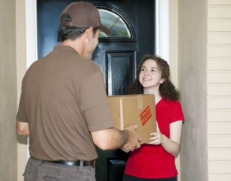 Teen girl receives package from friendly delivery man.   photo
