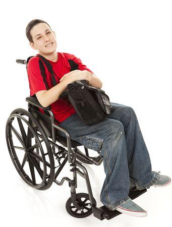十代の少年彼の車椅子に彼のバックパックで無効になっています。白のフルボディ isolted。 写真素材