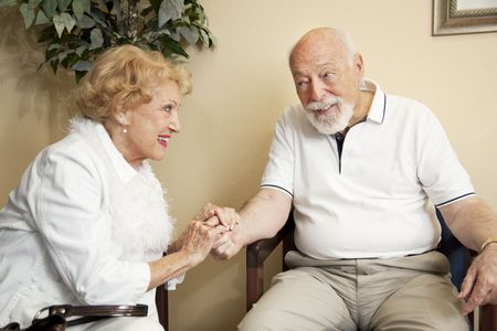 Senior couple in the waiting room of the doctors office holding hands for moral support. photo