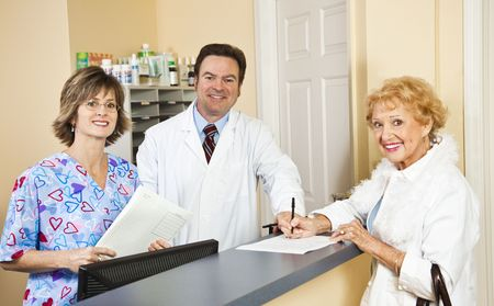 front desk: Doctor and his nurse receptionist greet a patient as she signs in and provides health insurance info.