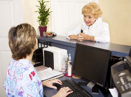 Pretty senior lady checking in at the doctors office reception desk.   Stock Photo