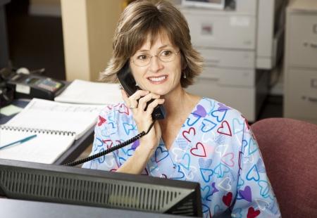 Bezet medische receptionist in de voorste bureau werkt bij een arts kantoor.   Stockfoto