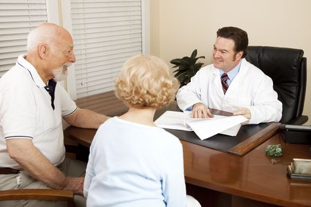 Doctor discussing treatment options with an elderly couple in his office.   photo