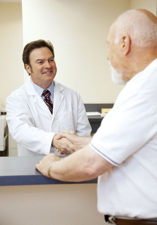 Beschrijvende arts een nieuwe patiënt begroeting op de voorste bureau. Stockfoto