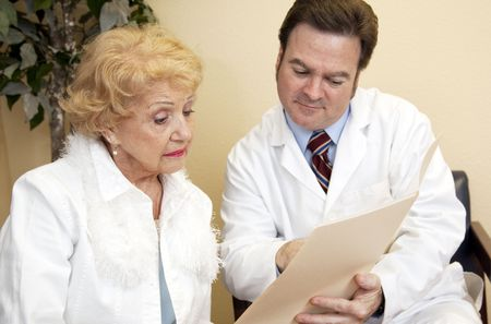 Senior woman learns from her doctor that her insurance wont cover treatment.   Stock Photo